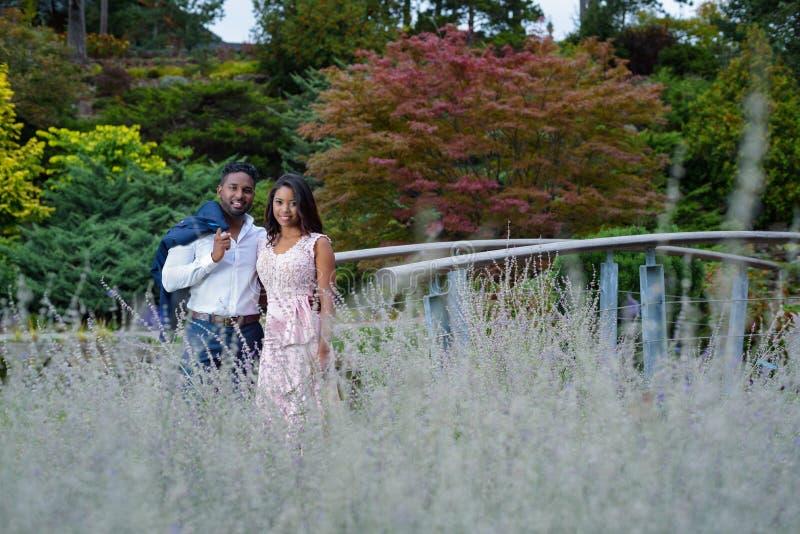 Förälskade barnpar krama sig i en lavendelträdgård royaltyfri bild