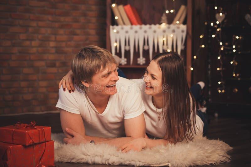 Förälskade härliga par lägger på golvet på jul arkivbilder
