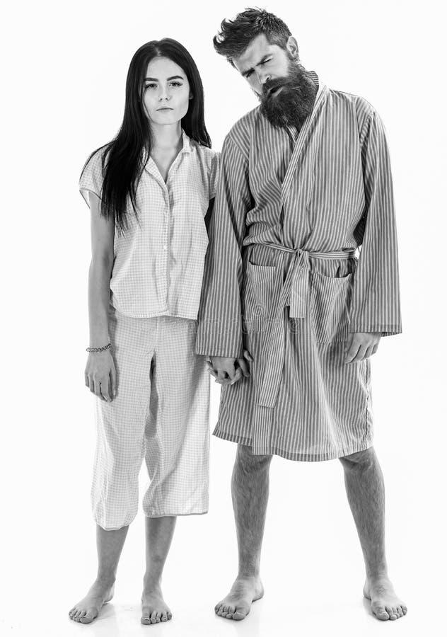 Förälskade hållhänder för par som isoleras på vit bakgrund Förälskat kela för unga sömniga par försiktigt i pyjamas arkivbilder