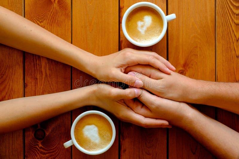 Förälskade innehavhänder för par i ett kafé, bästa sikt royaltyfri bild