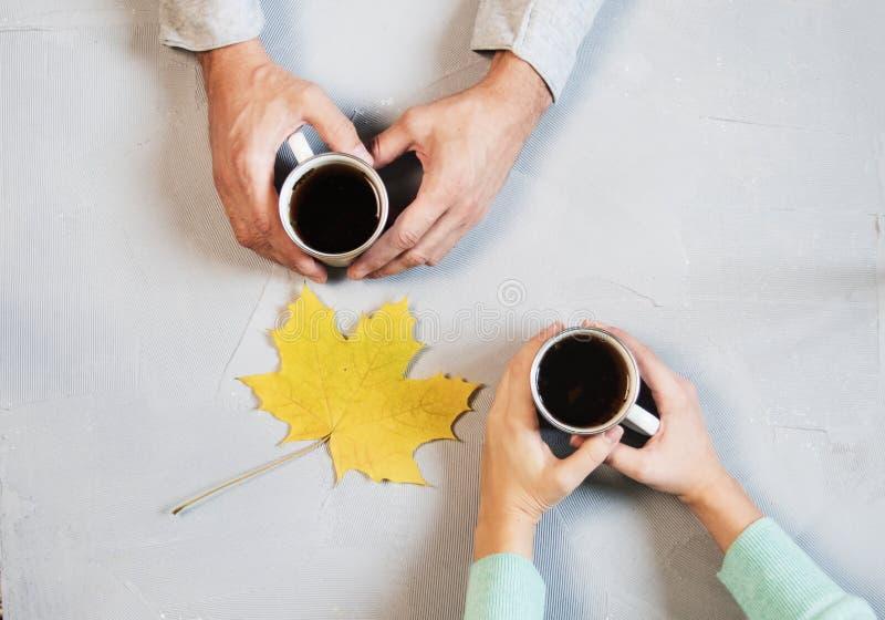 Förälskade innehavhänder för par med kaffe på den vita marmortabellen Fotografera taget från över, den bästa sikten med kopiering arkivbilder