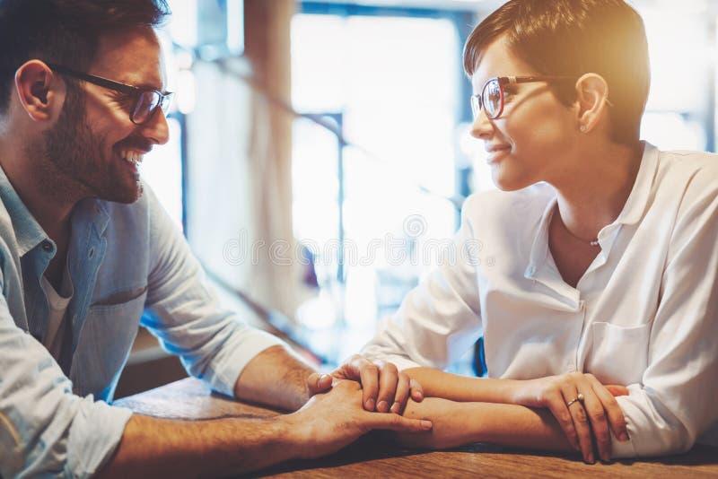 Förälskade innehavhänder för par som ser de och ler, medan sitta på kafét royaltyfria bilder