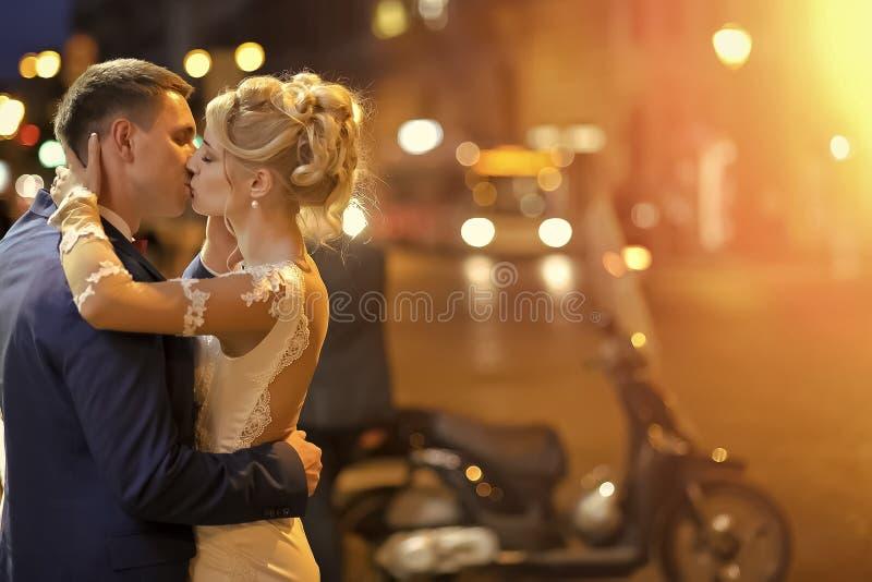 Förälskade kyssar för par Gifta sig par på nattstadsgatan fotografering för bildbyråer
