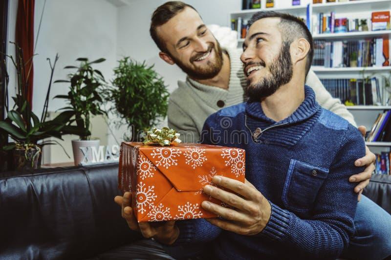 Förälskade lyckliga le unga stiliga glade par se de som firar och ger gåvan royaltyfri foto