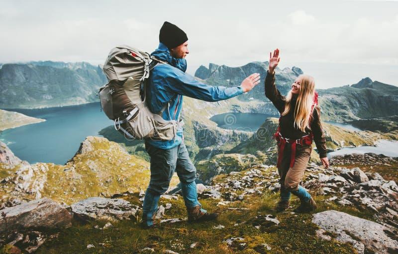 Förälskade lyckliga par ge fem händer på överkanten av berget arkivfoto