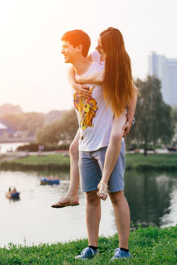 Förälskade lyckliga par ha rolig det fria som kramar att kyssa och ler piggybanking royaltyfria bilder