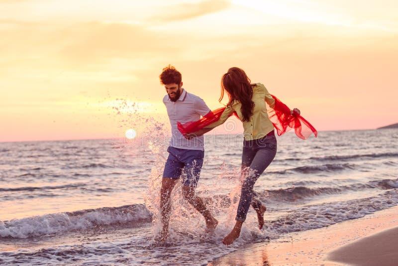 Förälskade lyckliga unga romantiska par har gyckel på den härliga stranden på den härliga sommardagen