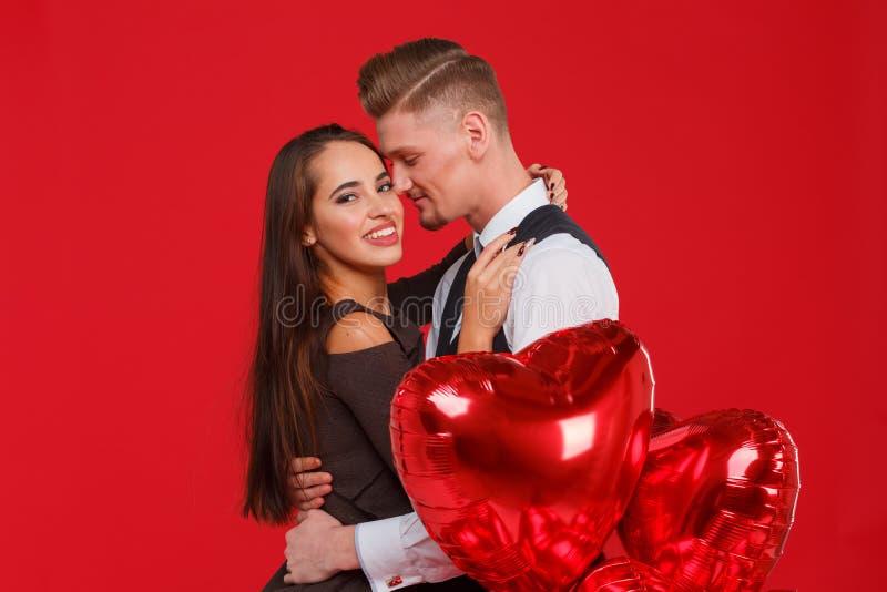 Förälskade omfamningar för ett ungt par, bredvid bollar i formen av en hjärta Röd bakgrund royaltyfria foton