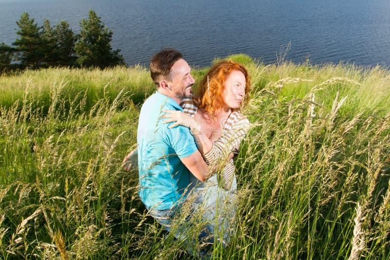 Förälskade par kramar passionately Lång-väntat på möte av de två vännerna utanför near av sjön Röd hårkvinna och mankram arkivbilder