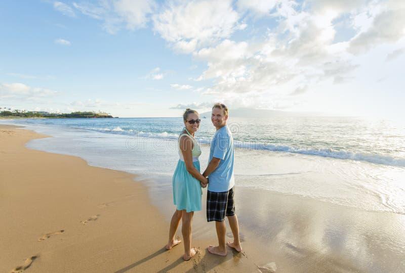 Förälskade par promenera stranden tillsammans fotografering för bildbyråer