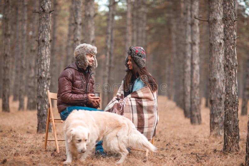 Förälskade par sitter i skog med en hund, meddelar, och drinkte från rånar royaltyfria bilder