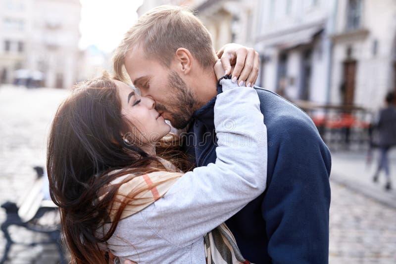 Förälskade par som kramar och kysser under staden, går royaltyfri bild