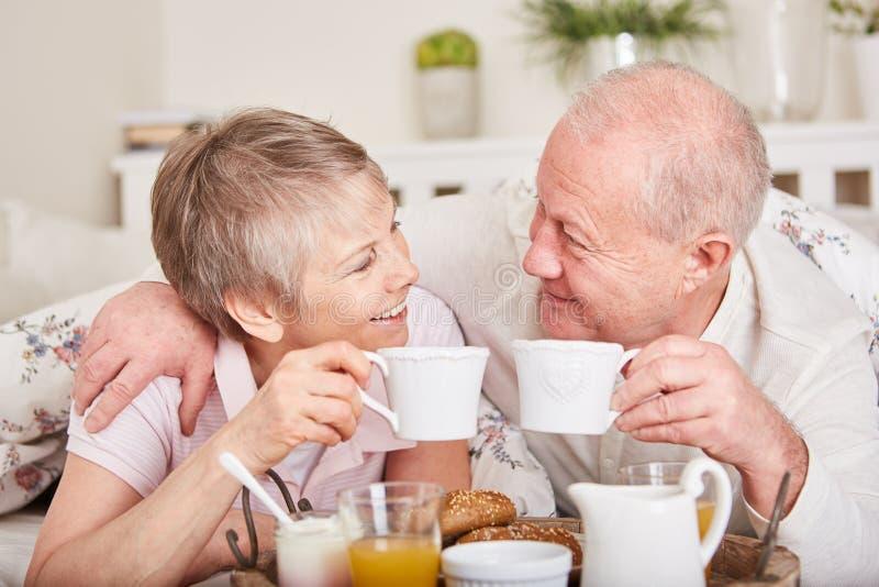 Förälskade pensionärer har frukosten tillsammans arkivfoton