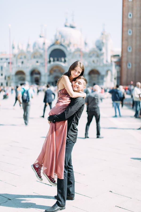Förälskade romantiska par ha gyckel som omfamnar och skrattar i Venedig, Italien på piazza, San Marco  fotografering för bildbyråer