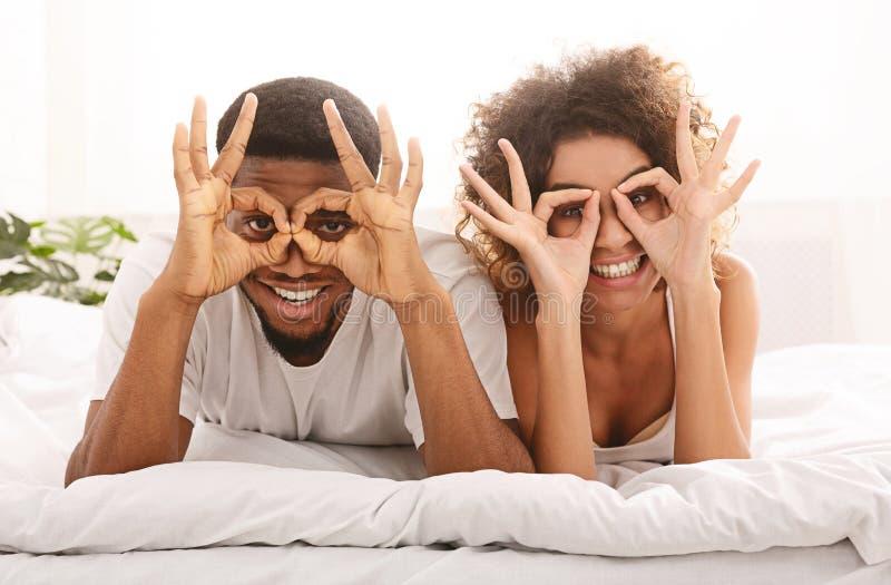 Förälskade rymmande fingrar för gladlynta lyckliga par nära ögon fotografering för bildbyråer
