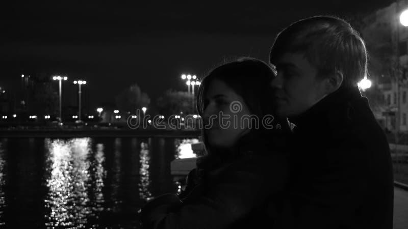 Förälskade ställningar för ett par mot ljusen av en nattstad på strand Fantastiska brölloppar nära floden på natten fotografering för bildbyråer
