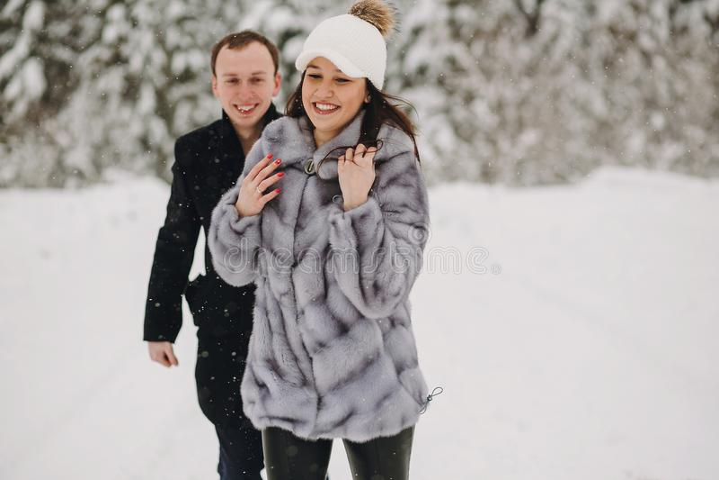 Förälskade stilfulla par ha gyckel i snöig berg Lycklig fami royaltyfri fotografi
