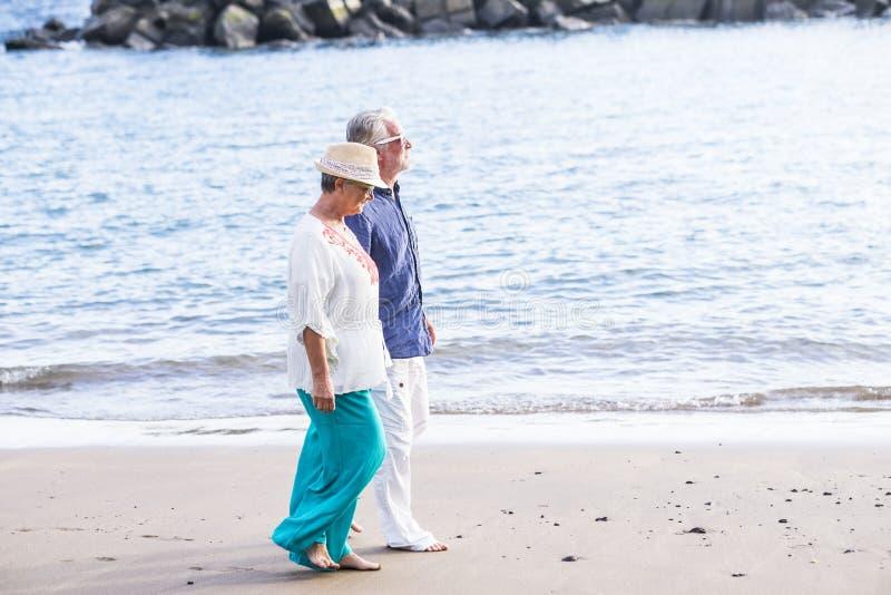 Förälskade tillsammans höga vuxna människor för lyckliga par som går på vågorna för ett hav för kust de propra tysta strand och f royaltyfria bilder