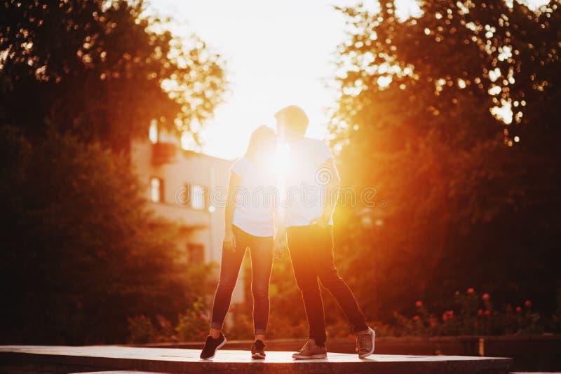 Förälskade tyckande om ögonblick för par under solnedgång royaltyfri fotografi