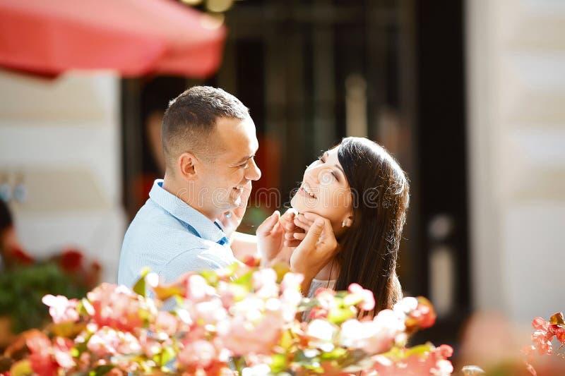 Förälskade unga par ha gyckel, att skratta och att le som är utomhus-, solig stående för vår, omfamning, lycklig le flicka arkivfoton