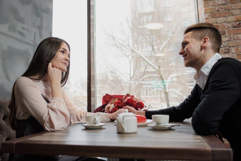 Förälskade unga par, mannen och kvinnan, sitter på en tabell i ett kafé St Dag för valentin` s fotografering för bildbyråer
