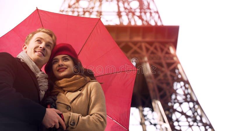 Förälskat anseende för lyckliga par under paraplyet i Paris och att ha romantisk semester fotografering för bildbyråer