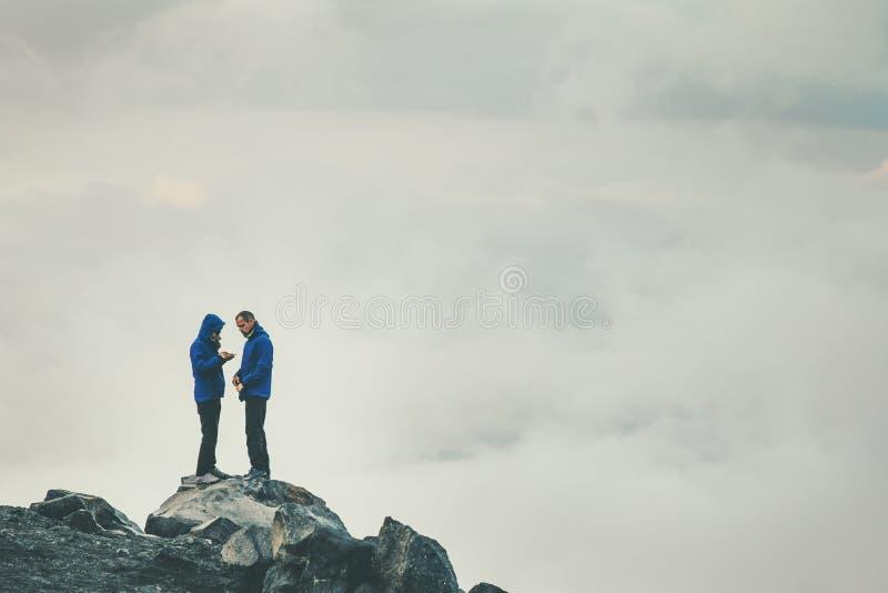 Förälskat anseende för parhandelsresande på klippan tillsammans arkivfoton