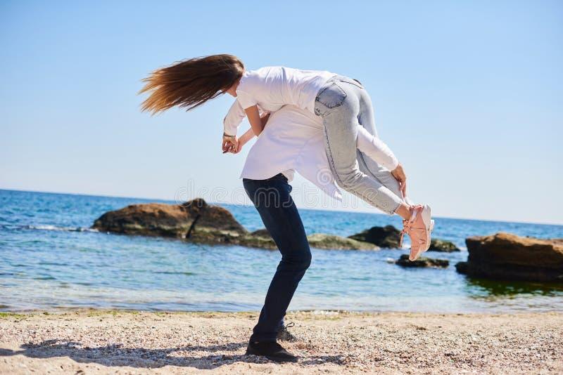 Förälskat bedra för par omkring på havet Lycksaliga par som kör ner stranden i solig dag royaltyfri fotografi