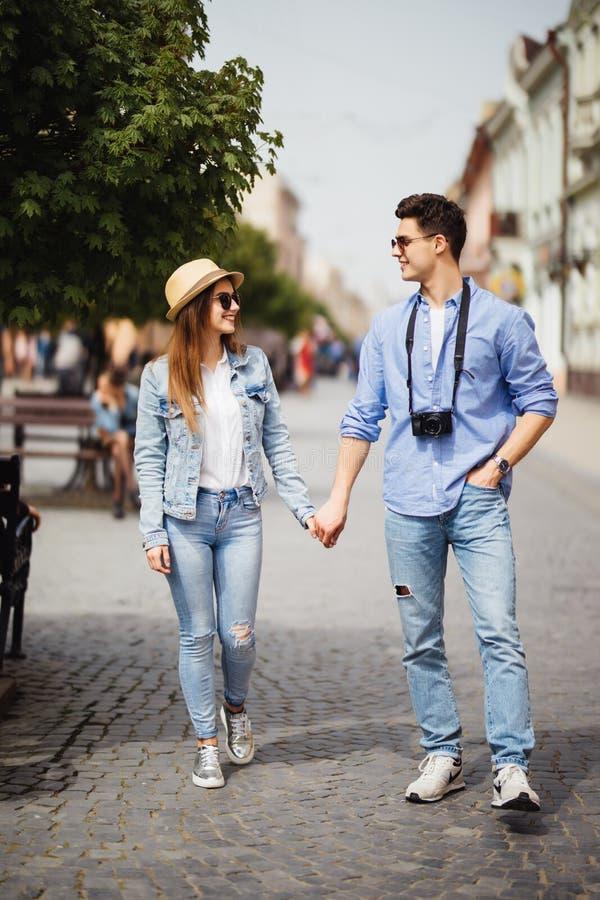 Förälskat gå för härliga turist- par på gatan tillsammans Lycklig ung man och lekvinna som går runt om gamla stadgator, Lo royaltyfri foto