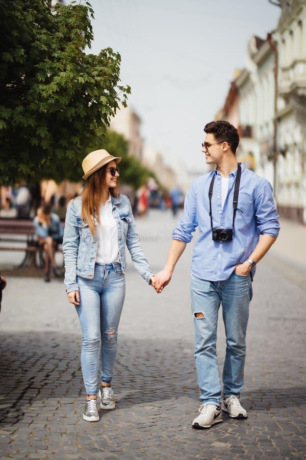 Förälskat gå för härliga turist- par på gatan tillsammans Lycklig ung man och lekvinna som går runt om gamla stadgator, Lo royaltyfria foton