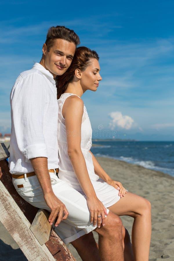 Förälskat gå för lyckliga par på stranden royaltyfria bilder