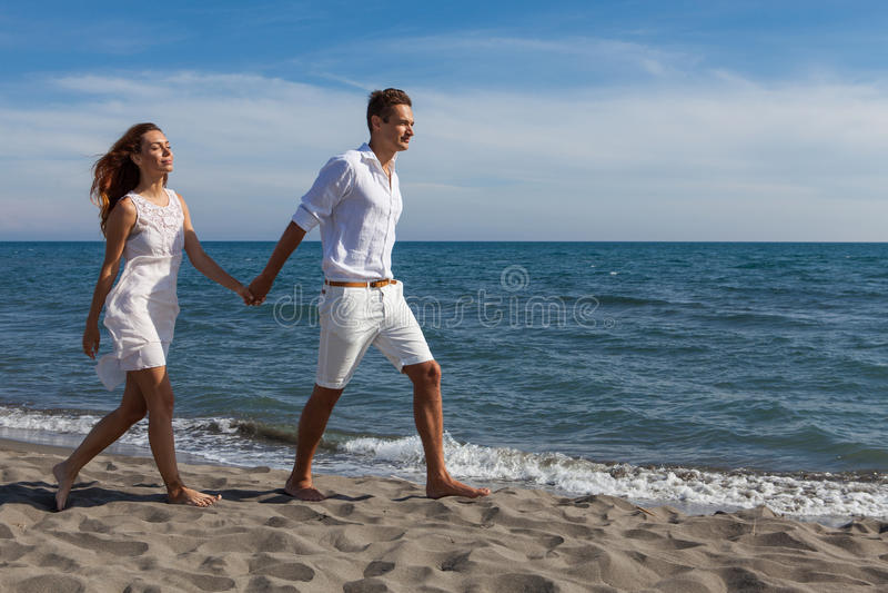 Förälskat gå för lyckliga par på stranden arkivfoton