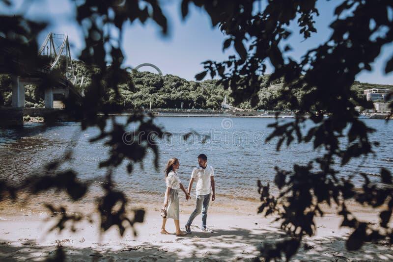 Förälskat gå för lyckliga stilfulla par på strandinnehavhänderna royaltyfri bild