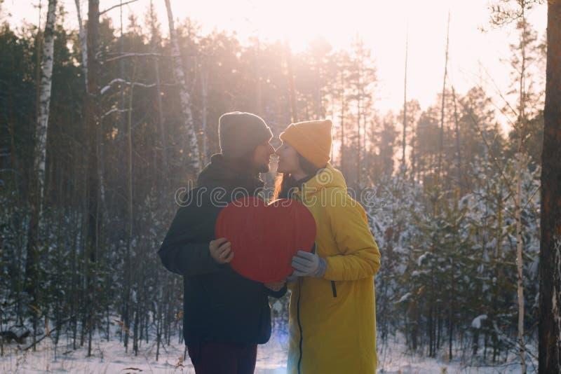 Förälskat innehav för par en stor röd hjärta på bakgrunden av den snöig skogen för vinter arkivfoto