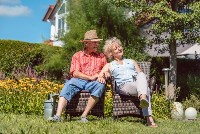 Förälskat koppla av för lyckliga höga par tillsammans i trädgården i a royaltyfri fotografi