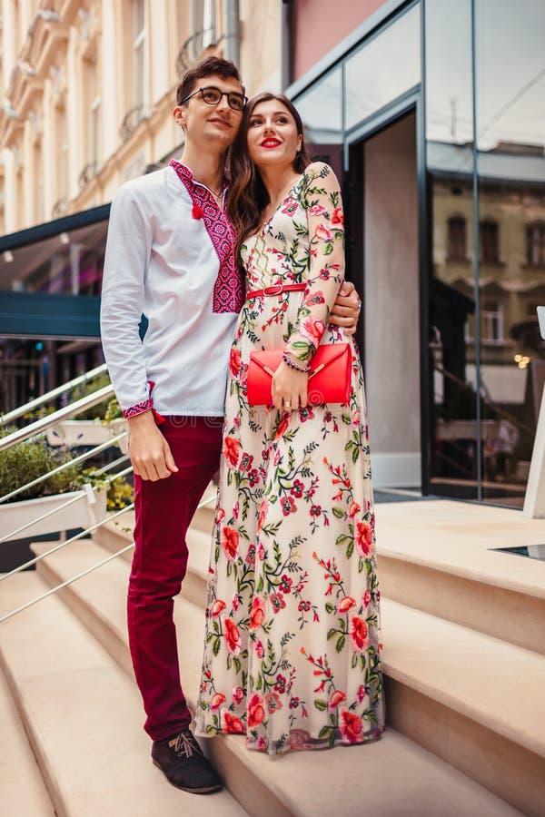 Förälskat krama för lyckliga par i centrum Bärande klänning och tillbehör för kvinna Mannen bär den traditionella ukrainska skjor fotografering för bildbyråer