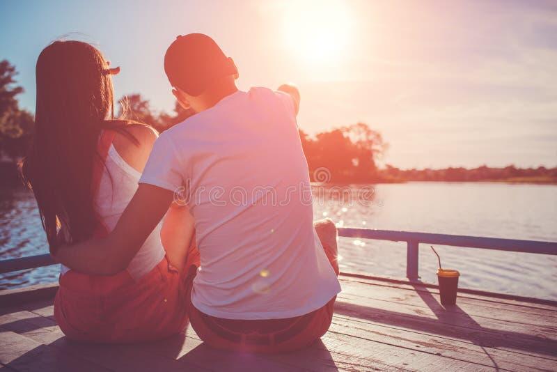 Förälskat krama för lyckliga par på flodskeppsdockan på solnedgången Ungdomarsom kyler vid vattnet royaltyfria bilder