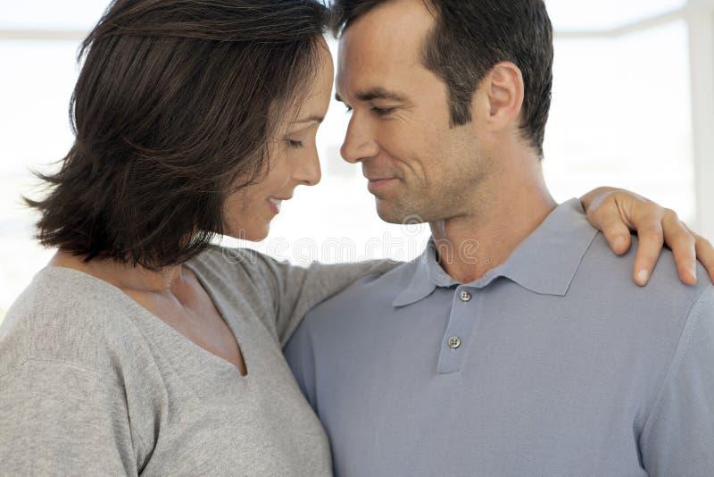 Förälskat krama för mellersta åldriga par - som är nära upp royaltyfri fotografi