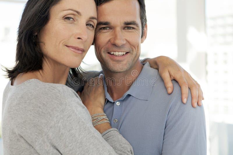 Förälskat krama för mellersta åldriga par - som är nära upp royaltyfria foton
