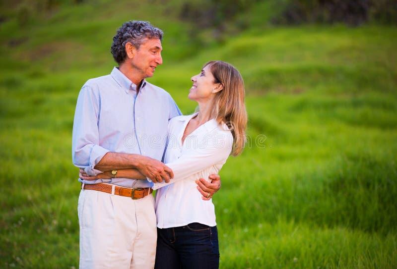 Förälskat krama för mogna mellersta ålderpar royaltyfri foto