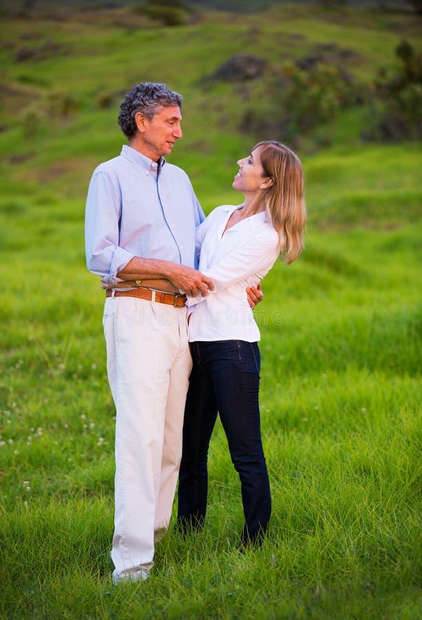 Förälskat krama för mogna mellersta ålderpar arkivbild