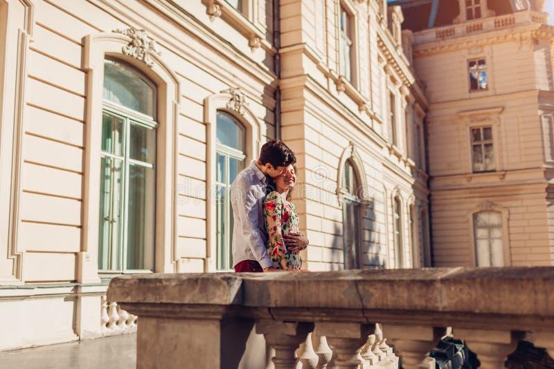 Förälskat krama för unga lyckliga par utomhus Romantisk man och kvinna som går vid gammal stadsarkitektur royaltyfri fotografi