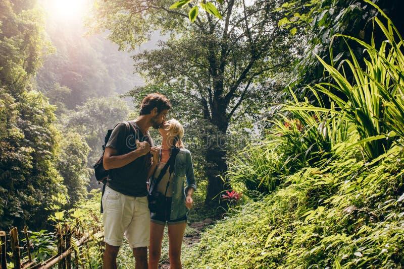 Förälskat kyssa för par, medan fotvandra royaltyfri bild