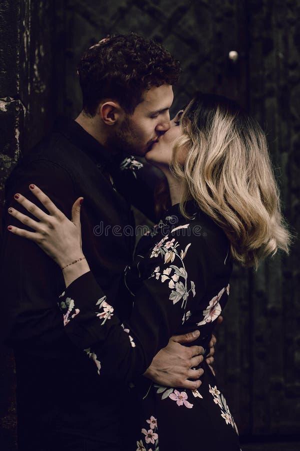 Förälskat kyssa för stilfulla par i aftonstadsgata modern wo royaltyfria bilder