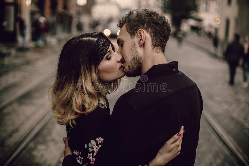 Förälskat kyssa krama för stilfulla zigenska par i aftonstadsstr royaltyfria foton