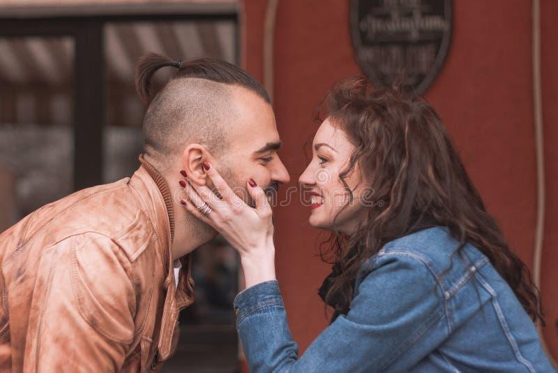 Förälskat kyssa sitta för lyckliga par på en tabell i ett stadskafé royaltyfri fotografi