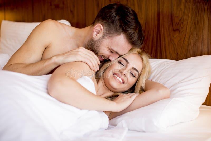 Förälskat ligga för romantiska par i säng tillsammans royaltyfri foto