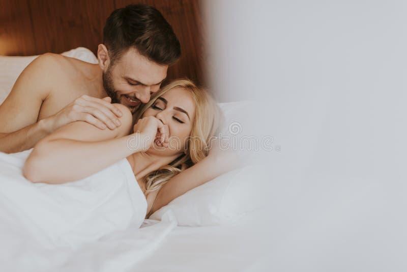 Förälskat ligga för romantiska par i säng tillsammans royaltyfria foton