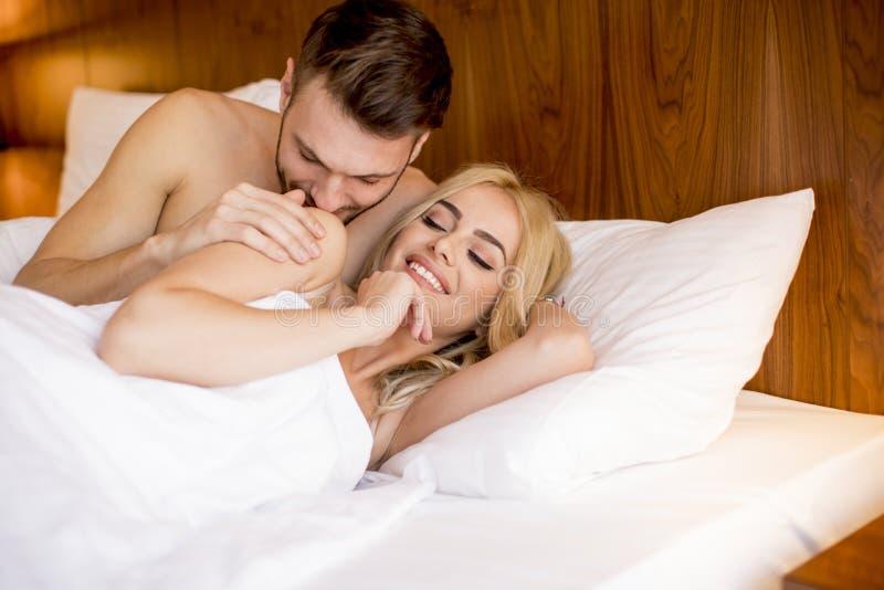 Förälskat ligga för romantiska par i säng tillsammans arkivbilder