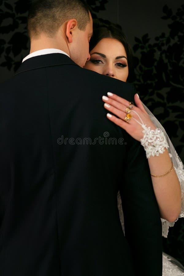 Förälskat omfamna för älskvärda par nära väggen arkivbild